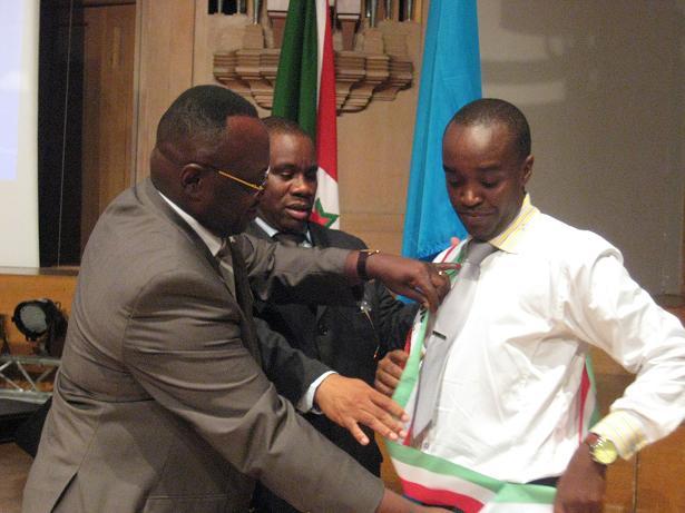 Jean-Marie Rurimirije et l'Ambassadeur Kavakure remettent l'écharpe aux couleurs nationales au représentant de la famille d'Albert Nibona