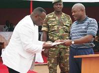 Jean-Marie Rurimirije recevant le Certificat de Mérite Patriotique des mains du chef de l'Etat Pierre Nkurunziza